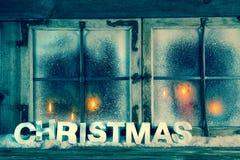 Atmosphärisches altes Weihnachtsfenster mit roten Kerzen und Text Lizenzfreies Stockbild
