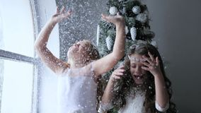 Atmosphere of new year, little girls have fun with artificial snow on winter photoshoot beside christmas tree stock video footage