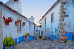 The atmosphere of old Obidos. The medieval street of walled town with rows of white houses with blue and yellow stripes, plants and flowers in pots and the hilly Royalty Free Stock Photo