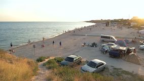 Atmosphere of summer holidays near the sea. People walk on the beach. Camping for vacationers. Atmosphere of summer holidays near the sea stock footage