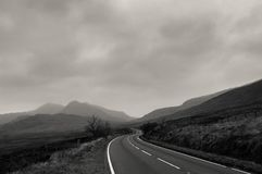 An atmospheric black and white edit of a road heading towards mountains on a stormy winters day. Snowdonia, Wales. UK. An atmospheric black and white edit of a royalty free stock image