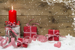 Atmospheric Christmas card with red burning candle and presents. On snowflake wooden background Stock Images