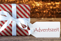 Atmospheric Christmas Gift With Label, Adventszeit Means Advent Season. Macro Of Christmas Gift Or Present On Atmospheric Wooden Background. Card For Seasons Stock Image