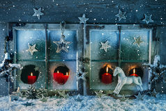 Atmospheric christmas window with red candles outdoor with snow. Idea for a greeting card. Royalty Free Stock Image