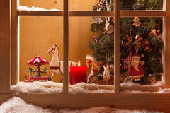 Atmospheric Christmas window sill decoration:snow,tre e,candle,rocking horse and carousel. Christmas window in red with carusel, wooden, horse, tree, santa claus royalty free stock photo