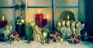 Atmospheric classic christmas decoration with angels, presents a. Nd red candles in an old wooden window Royalty Free Stock Image