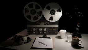 Retro Analog Quarter Inch Tape Recorder Being Operated in a Darkened Room. Atmospheric film noir style shots of an analog quarter inch tape recorder being stock footage