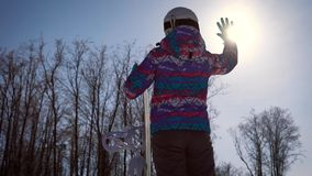 Atmospheric frame, the concept of dreams and joy of the day. A snowboarder girl catches a bright sun with her hand. A. Clear winter day in the mountains in a stock video