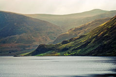 Atmospheric hills and lake. A beautiful and calm lake with a hill in the background Stock Photos