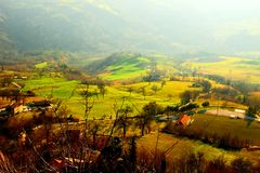 Hilly landscape partly covered with fog and bathed in sunlight royalty free stock photo