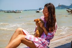 Atmospheric lifestyle candid photo of young beautiful asian woman on vacation plays with a cat. royalty free stock photography