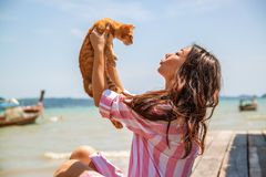Atmospheric lifestyle candid photo of young beautiful asian woman on vacation plays with a cat. stock photos