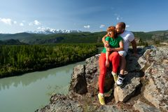 Atmospheric moment for lovers in the mountains. Hiking women and men sitting on the top of the mounting and looking at a beautiful landscape. Travel Lifestyle royalty free stock photography
