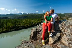 Atmospheric moment for lovers in the mountains. Hiking women and men sitting and kissing on the top of the mounting and looking at a beautiful landscape royalty free stock image