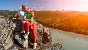 Atmospheric moment for lovers in the mountains. Hiking women and men sitting and kissing on the top of the mounting and looking at a beautiful landscape stock photos