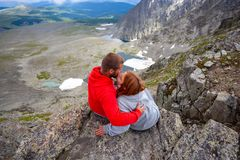 Atmospheric moment for lovers in the mountains. Hiking women and men standing on the top of the mounting and looking at a beautiful landscape. Travel Lifestyle royalty free stock photo