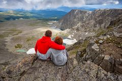 Atmospheric moment for lovers in the mountains. Hiking woman and man standing on the top of the mounting and looking at a beautiful landscape. Travel Lifestyle stock photo