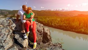 Atmospheric moment for lovers in the mountains. Hiking women and men sitting on the top of the mounting and looking at a beautiful landscape. Travel Lifestyle stock photography