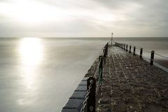Atmospheric and Moody Long Exposure Photograph of Stone Pier at Brighton, East Sussex, England, UK with copy space.  Royalty Free Stock Image