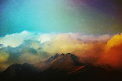 Atmospheric mountain peaks in low clouds. Atmospheric grunge textured image of clouds rolling in over mountain peaks in Aoraki National Park Royalty Free Stock Images