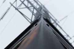 Closeup atmospheric photo of the high voltage transmission tower covered with hoarfrost standing on the gray sky Stock Photo
