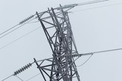 Closeup atmospheric photo of the high voltage transmission tower standing on the gray sky background after blizzard Stock Photo