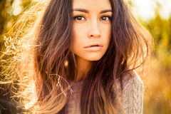 Atmospheric portrait of beautiful young lady. Outdoor atmospheric fashion photo of young beautiful lady. Brown hair and eyes. Warm autumn. Warm spring stock photo