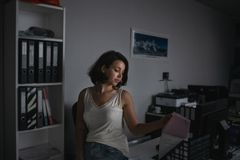 Atmospheric portrait of young seductiveworker holding docs at her workplace in evening. Overtime work concept. Atmospheric portrait of young seductiveworker royalty free stock image