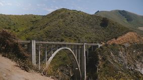 Atmospheric scenic wide shot of car traffic on iconic Bixby Canyon Bridge, Highway One in famous Big Sur California USA. Background shot, famous piece of stock footage