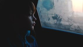 Atmospheric shot of little 4-6 year old thoughful Caucasian boy looking out of foggy car window in dusk dark evening. Beautiful cinematic close-up of male stock footage