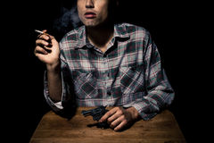 Atmospheric shot of man with gun smoking cigarette Royalty Free Stock Images