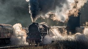 Atmospheric steam train. Steam train locomotive approaching a station passing through a goods yard letting of smoke and steam lit from behind creating Stock Image