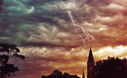 Atmospheric stormy sky and lightning over church. Atmospheric grunge textured stormy sky and lightning over a church spire. Abbotsford Convent, Melbourne Royalty Free Stock Photos