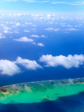 The atoll in ocean through clouds. Aerial view.Landscape in a sunny day Royalty Free Stock Photography