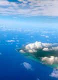 The atoll ring in ocean. Landscape in a sunny day. The atoll ring in ocean is visible through clouds. Aerial view royalty free stock photo