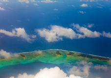 The atoll ring at ocean is visible through clouds. Royalty Free Stock Photos