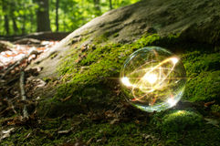 Atom Crystal Ball Nature. Magic crystal ball atom on forest floor for summer fantasy imagery Royalty Free Stock Photography