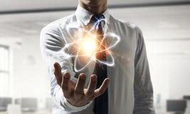 Atom ikona w palmie Obrazy Royalty Free