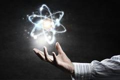 Atom ikona w palmie Mieszani środki Fotografia Royalty Free