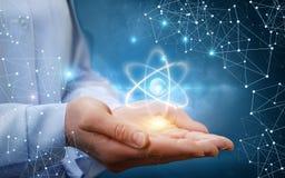 Atom molecule in female hands. Atom molecule in female hands on a blue background stock image
