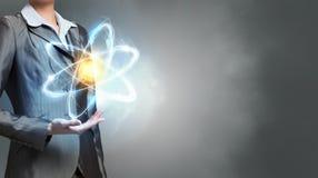 Atom molecule in hands . Mixed media Royalty Free Stock Image