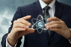 Atom shows in the hands of the businessman . royalty free stock photography