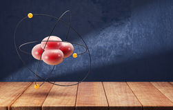 Atom on the wooden table on dark blue background Stock Image
