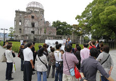The Atomic Bomb Dome at Hiroshima. HIROSHIMA,JAPAN-OCTOBER 14:A Guide having a presentation at Atomic Bomb Dome at Hiroshima Peace Memorial Park in Japan on Stock Photography