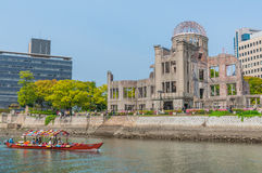 Atomic Bomb Dome. Hiroshima, Japan - April 28, 2013: Tourists walk between the river and Royalty Free Stock Photography
