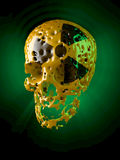 Atomic skull, rotten. Rotten, yellow lacquered skull with black radioactive sign, green glowing illumination Royalty Free Stock Photo