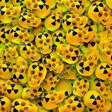 Atomic skulls. Green lit heap, poll of yellow lacquered skulls with black radioactive sign, 3d rendering Royalty Free Stock Images