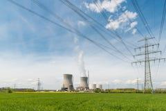 Atomkraftwerk mit grünem Feld und elektrischem Hochspannungsw Lizenzfreies Stockbild