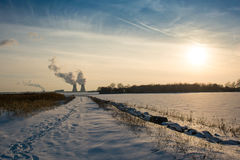 Atomkraftwerk nahe bei untergehender Sonne im Winter Stockbilder