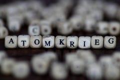 ATOMKRIEG słowo pisać na drewnianym sześcianie z kostka do gry tłem Zdjęcia Royalty Free
